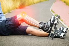 Injured skater with painful leg. Injured skater sitting with his painful leg Royalty Free Stock Photo