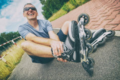 Injured skater with painful leg. Injured skater sitting and holding his painful leg Royalty Free Stock Images