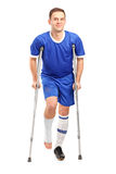 Injured soccer football player on cru. Full length portrait of an injured soccer football player on crutches  against white background Stock Images