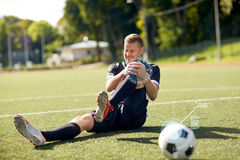 Injured soccer player with ball on football field. Sport, sports injury and people - injured soccer player with ball on football field Stock Image