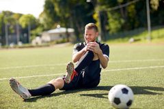 Injured soccer player with ball on football field. Sport, football training, sports injury and people - injured soccer player with ball on field Royalty Free Stock Photo