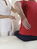 Injured Sportsman being helped by therapist. Injured sportsman discussing injury with female sport massage therapist Royalty Free Stock Photo