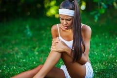 Injured sportswoman sitting on the grass Stock Photo