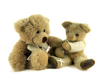 Injured teddy. Teddy with arm in a sling and plaster on leg being comforted Royalty Free Stock Photo