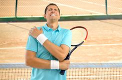 Injured tennis player. Shot of a tennis player with a shoulder injury on a clay court royalty free stock images