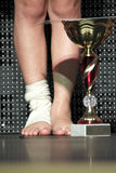 Injured winner's legs with a golden cup. Low section of winner in competition having feet trauma royalty free stock photography