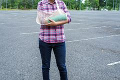 Injured woman with broken arm wearing an arm sling and green cas. T on arm standing in public park Stock Images