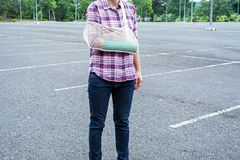 Injured woman with broken arm wearing an arm sling and green cas. T on arm standing in public park Royalty Free Stock Photo