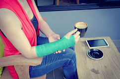 Injured woman with green cast on the wrist holding black coffee Royalty Free Stock Photography