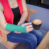 Injured woman with green cast on the wrist holding black coffee Royalty Free Stock Photos