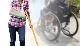 Injured woman standing with green cast on arm and arm sling usin. G wood crutches isolated on blurred background seniors woman sitting in wheelchair, clipping Stock Photo