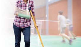 Injured woman  standing with green cast on arm and arm sling usi. Ng wood crutches, insurance concept Stock Photo