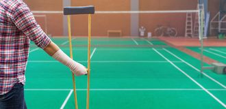 Injured woman standing wearing shirt and jeans with arm splint a. Nd holding wooden crutches isolated on green badminton court stock images