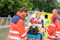 Injured woman talking with paramedics emergency. Patient talking with paramedics after accident aid emergency arm injury royalty free stock images