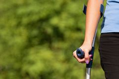 Injured woman trying to walk on crutches royalty free stock photos