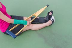 Injured woman wearing sportswear  painful arm with gauze bandage, arm cast and wooden crutches sitting on floor.  Stock Photo