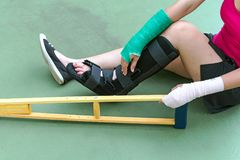 Injured woman wearing sportswear  painful arm with gauze bandage, arm cast and wooden crutches sitting on floor.  Stock Images