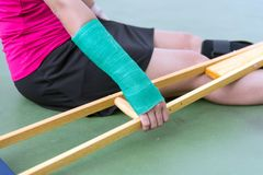 Injured woman wearing sportswear  painful arm with gauze bandage, arm cast and wooden crutches sitting on floor.  Royalty Free Stock Photos