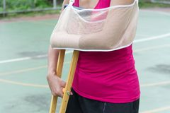 Injured woman wearing sportswear  painful arm with gauze bandage. Arm sling and wooden crutches on basketball court Royalty Free Stock Photos