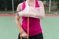 Injured woman wearing sportswear painful arm with gauze bandage, Royalty Free Stock Photography