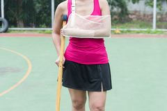 Injured woman wearing sportswear  painful arm with gauze bandage. Arm sling and wooden crutches on basketball court Stock Photo