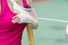 Injured woman wearing sportswear  painful arm with gauze bandage. Arm sling and wooden crutches on basketball court Stock Photography