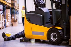 An injured worker after an accident in a warehouse. An accident in a warehouse. Woman running towards her colleague lying on the floor next to a forklift Stock Images