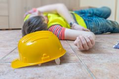 Injured worker had accident. Man is lying on the floor. Yellow helmet in front Royalty Free Stock Photos