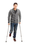 Injured young man on crutches. Full length portrait of an injured young man on crutches on white background royalty free stock photo