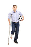 Injured young man on crutches holding a ball. Full length portrait of an injured young man on crutches holding a football on white background stock photo