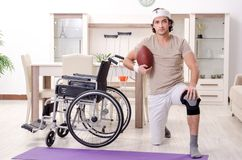 The injured young man doing exercises at home stock photos