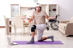 The injured young man doing exercises at home. Injured young man doing exercises at home stock image