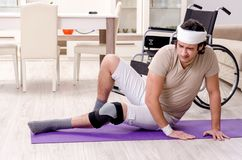 Injured young man doing exercises at home stock images