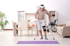 Injured young man doing exercises at home royalty free stock image