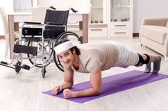 The injured young man doing exercises at home. Injured young man doing exercises at home stock photo
