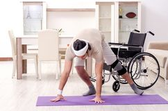 The injured young man doing exercises at home. Injured young man doing exercises at home stock photos