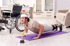 The injured young man doing exercises at home. Injured young man doing exercises at home royalty free stock photos