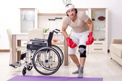 The injured young man doing exercises at home. Injured young man doing exercises at home royalty free stock photo