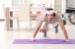Injured young man doing exercises at home stock image
