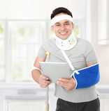 Injured young man holding a tablet Stock Photos