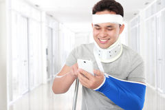 Injured young man look happy play smartphone Royalty Free Stock Photography