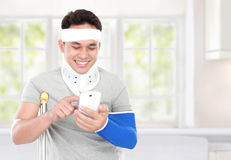 Injured young man look happy play smartphone Royalty Free Stock Image