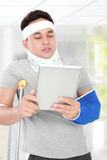 Injured young man look serious use the tablet Royalty Free Stock Image