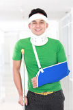 Injured young man use crutch and arm sling Royalty Free Stock Photography