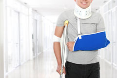 Injured young man use crutch and arm sling. Portrait of injured young man use crutch and arm sling Stock Image