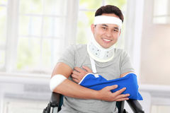 Injured young man in wheelchair with cross arm Stock Image