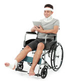 Injured young man in wheelchair play gadget Stock Images