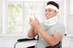 Injured young man in wheelchair play on his smartphione Stock Image