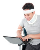 Injured young man in wheelchair work on laptop Royalty Free Stock Images