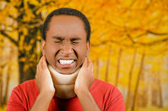 Injured young positive black hispanic male wearing neck brace, holding hands in pain around support making faces of. Agony, yellow abstract background Stock Photos